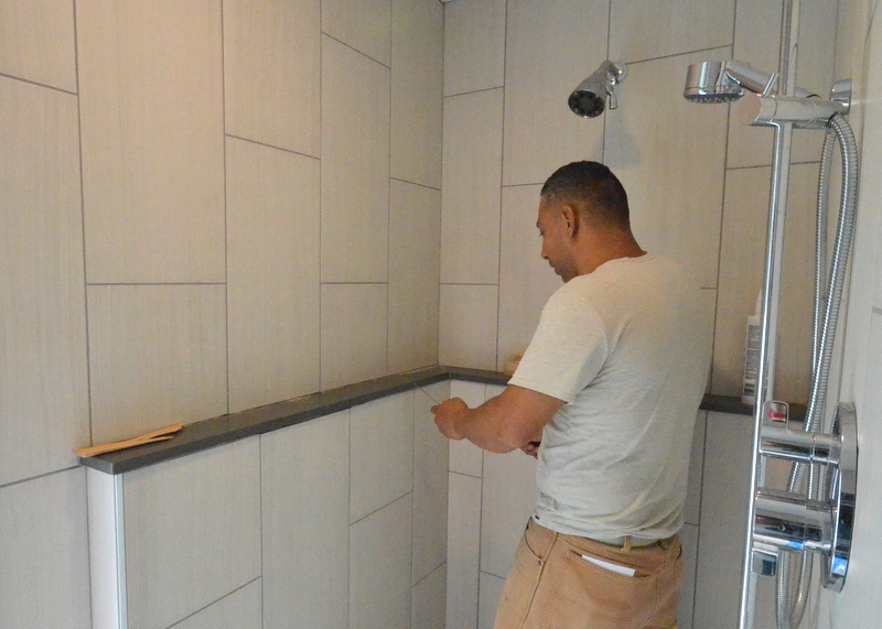 Joe begins with a painter's blade, scraping grout out of the joint under the shelf.