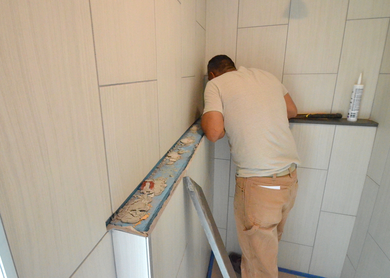 That reveals the spacers and dried epoxy grout used to mount the shelf -- and the blue waterproofing used to seal the structure of the shower stall.