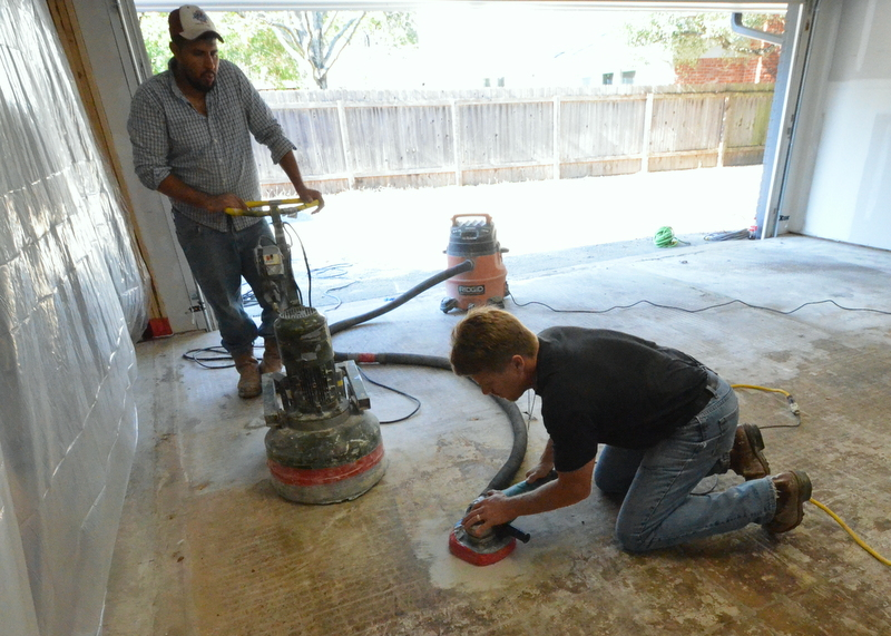 On his knees, Monty uses a heavy grinder to test clean a small section of the floor. Jose supervises.