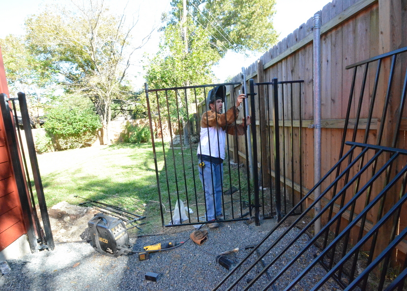 While Victor wrangles cedar in the front yard, Victor is in back cutting, grinding and welding the metal fencing and gates. Here, one side panel is already up as he test fits one of the gate panels.