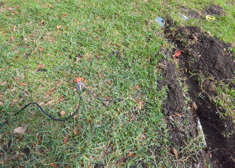 Darynn and Mikel made waterproof connections between the new and old control wires. The trench at right is where Mikel discovered the open end of a sprinkler line that was severed during construction of the garage. He cut off the knife edge of the PVC and capped it off.
